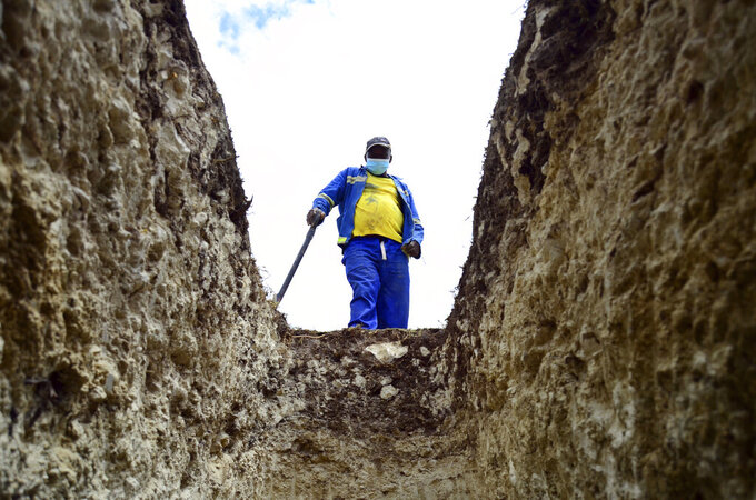 A grave digger looks into a grave at the Motherwell Cemetery in Port Elizabeth, South Africa, Friday, Dec. 4, 2020. Health Minister Zweli Mkhize announced on Wednesday, Dec. 9, 2020 that the country is now experiencing a Covid-19 pandemic second wave. (AP Photo/Theo Jeftha)