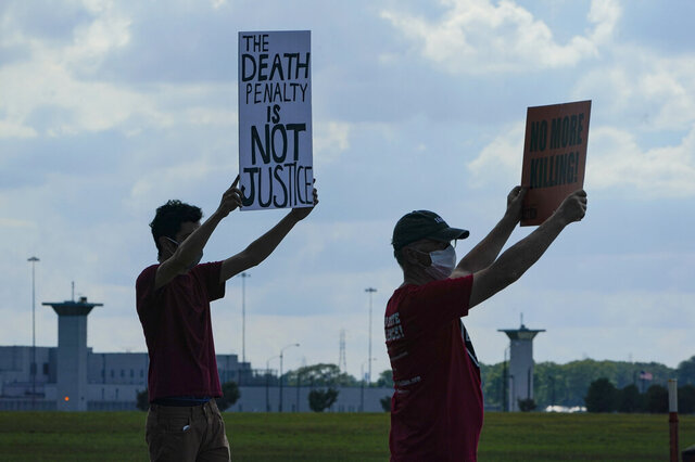 Death penalty protestors hold up signs across the street from the federal prison complex in Terre Haute, Ind., Wednesday, Aug. 26, 2020. Lezmond Mitchell, the only Native American on federal death row, is set to die Wednesday for the slayings of a 9-year-old and her grandmother nearly two decades ago. (AP Photo/Michael Conroy)