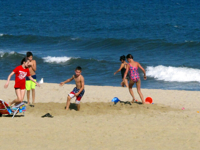 Children play in a hole they dug Monday, Sept. 28, 2020, on a section of beach in Long Branch, N.J., where a replenishment project is due to begin this week. The $20 million project will widen beaches in Long Branch, Monmouth Beach and Sea Bright. (AP Photo/Wayne Parry)
