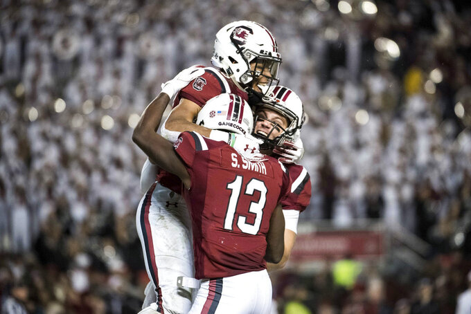 South Carolina quarterback Jake Bentley, right, Shi Smith (13), and A.J. Turner celebrate a touchdown during the first half of an NCAA college football game against Chattanooga on pSaturday, Nov. 17, 2018, in Columbia, S.C. South Carolina defeated Chattanooga 49-9. (AP Photo/Sean Rayford)