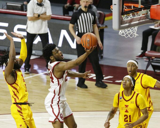 Oklahoma's Elijah Harkless (24) takes a shot against Iowa State's Tre Jackson (3), Jaden Walker (21), and Javan Johnson (13) during the second half of an NCAA college basketball game in Norman, Okla., Saturday, Feb. 6, 2021. (AP Photo/Garett Fisbeck)