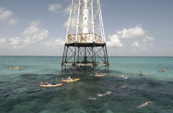 In this photo provided by the Florida Keys News Bureau, competitors in the Swim for Alligator Lighthouse, an open-water, long-distance event, round the Florida Keys lighthouse and head to shore Saturday, Sept. 11, 2021, near Islamorada, Fla. The event began in 2013 to help raise awareness about preserving the almost 150-year-old lighthouse as well as five other lighthouses off the Keys. This year's contest attracted 461 swimmers. (Steve Panariello/Florida Keys News Bureau via AP)