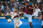 Toronto FC forward Patrick Mullins (13) chases the ball against Colorado Rapids defender Auston Trusty in the first half of an MLS soccer game in Denver, Saturday, Sept. 25, 2021. (AP Photo/Joe Mahoney)