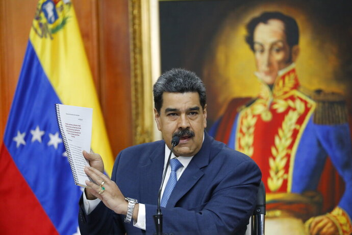Venezuelan President Nicolas Maduro holds up a copy of his country's case taken to the International Criminal Court regarding U.S. sanctions during a press conference at Miraflores presidential palace in Caracas, Venezuela, Friday, Feb. 14, 2020. Venezuela is demanding that Washington stop piling on punishing financial sanctions aimed at forcing a regime change in Venezuela. The international court must next decide whether it will open an investigation. (AP Photo/Ariana Cubillos)