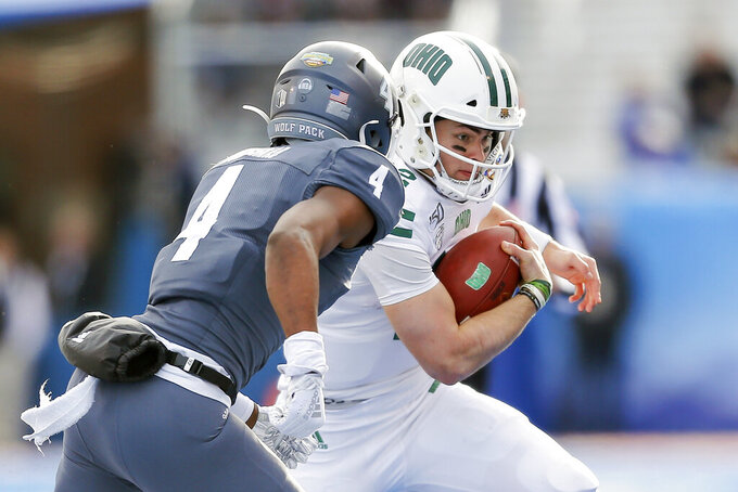 Ohio quarterback Nathan Rourke, right, runs with the ball as Nevada defensive back EJ Muhammad (4) closes in for a tackle-attempt in the first half of the Famous Idaho Potato Bowl NCAA college football game Friday Jan. 3, 2020, in Boise, Idaho. (AP Photo/Steve Conner)