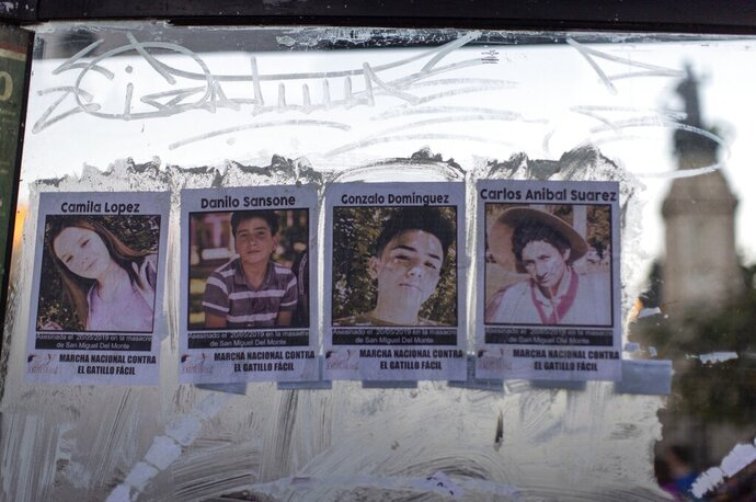 Posters of the four victims of Monday's police shooting, from left, Camila Lopez, Danilo Sansone, Gonzalo Dominguez and Carlos Anibal Suarez are glued to a bus stop, in Buenos Aires, Argentina, Friday, May. 24, 2019. Argentines protested after officers on Monday fired shots that led to the deaths of the three teenagers and a young man in a car chase. (AP Photo/Tomas F. Cuesta)