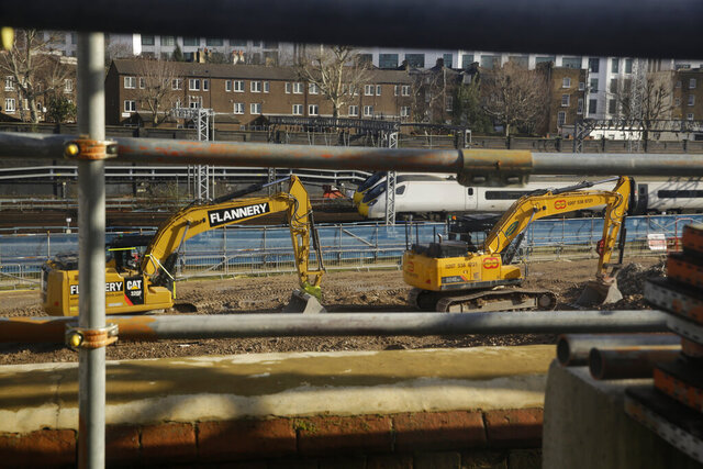 Trains are seen through a viewing window passing tracked excavator machinery on the construction site of the High Speed 2 (HS2) rail line at Euston station in London, Tuesday, Feb. 11, 2020. Britain's Conservative government is set to approve a contentious, expensive plan for a high-speed rail line linking London with central and northern England, despite opposition from environmentalists and even some members of the governing party. (AP Photo/Matt Dunham)