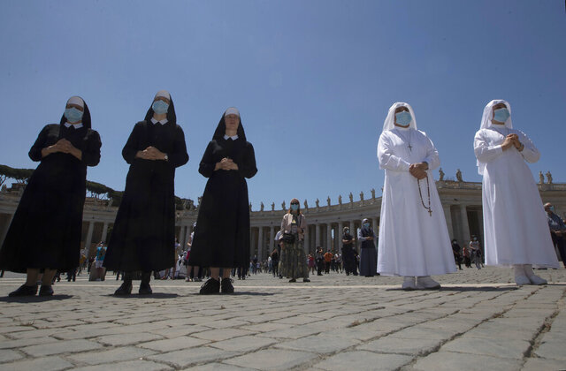 Nuns and faithful gather in St. Peter's Square at the Vatican, Sunday, May 31, 2020. Pope Francis has cheerfully greeted people in St. Peter's Square on Sunday, as he resumed his practice of speaking to the faithful there for the first time since lockdown began in Italy and at the Vatican in early March. Instead of the tens of thousands of people who might have turned out on a similarly brilliantly sunny day like this Sunday, in pre-pandemic times, perhaps a few hundred came to the square, standing well apart from others or in small family groups. (AP Photo/Alessandra Tarantino)