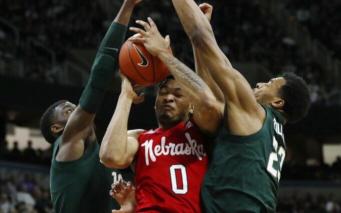 Nebraska guard James Palmer Jr., center, loses control of the ball after running into Michigan State forwards Gabe Brown, left, and Xavier Tillman, right, during the first half of an NCAA college basketball game, Tuesday, March 5, 2019, in East Lansing, Mich. (AP Photo/Carlos Osorio)