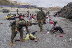 A migrant is assisted by soldiers of the Spanish Army near the border of Morocco and Spain, at the Spanish enclave of Ceuta, on Tuesday, May 18, 2021. (AP Photo/Bernat Armangue)