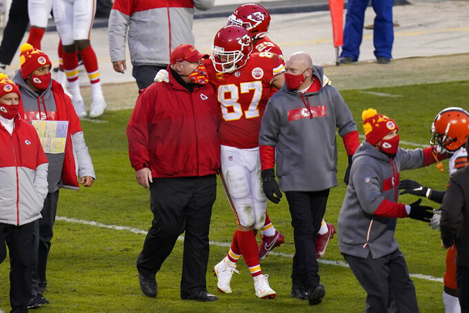 Kansas City Chiefs tight end Travis Kelce (87) walks off the field with head coach Andy Reid after an NFL divisional round football game against the Cleveland Browns, Sunday, Jan. 17, 2021, in Kansas City. The Chiefs won 22-17. (AP Photo/Orlin Wagner)