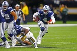 Dallas Cowboys quarterback Dak Prescott (4) scrambles as New Orleans Saints defensive end Marcus Davenport (92) is shoved to the turf by Cowboys offensive tackle Tyron Smith (77) in the first half of an NFL football game in New Orleans, Sunday, Sept. 29, 2019. (AP Photo/Butch Dill)