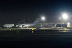 A charter flight transporting passengers from the quarantined Diamond Princess cruise ship moves behind military airplanes after it arrived at Travis Air Force Base in Fairfield, Calif., Sunday, Feb. 16, 2020. (AP Photo/Hector Amezcua)