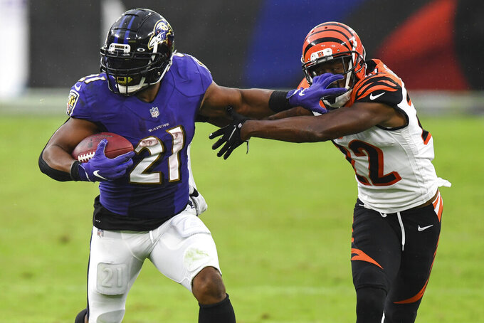 File-This Oct. 11, 2020, file photo shows Baltimore Ravens running back Mark Ingram (21) running the ball against Cincinnati Bengals cornerback William Jackson (22) during the second half of an NFL football game in Baltimore. The three-time Pro Bowl running back has been released by the Baltimore Ravens, who used the 10-year veteran as a starter for the first seven games this season before dropping him deep on the depth chart. (AP Photo/Terrance Williams, File)