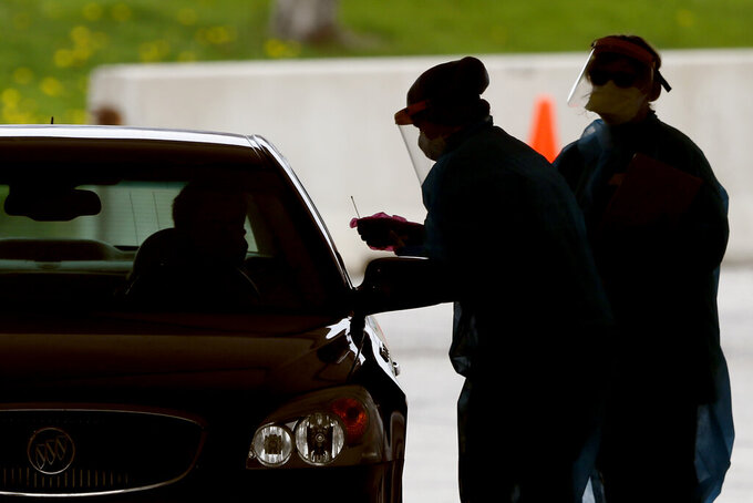 "FILE - In this May 1, 2020, file photo, medical workers test a local resident at a drive-thru COVID-19 testing site in Waterloo, Iowa. Newly released records show the State of Iowa deployed ""strike teams"" to conduct rapid on-site coronavirus testing at 17 businesses in 2020, including some of the state's most powerful pork and beef companies. (AP Photo/Charlie Neibergall, File)"