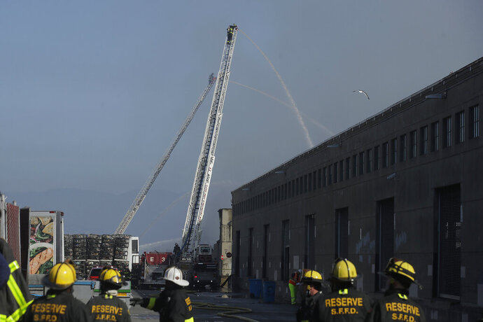 A firefighter sprays into a warehouse after a fire broke out before dawn at Fisherman's Wharf in San Francisco, Saturday, May 23, 2020. Fire officials said no injuries have been reported Saturday morning and firefighters are making multiple searches to ensure no one was inside the building on Pier 45. (AP Photo/Jeff Chiu)