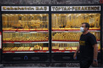 A man walks past a gold shop in Istanbul, Friday, Aug. 7, 2020. Turkey's currency tumbled further Friday, hitting another record low. The Turkish lira dropped to 7.3677 against the dollar before making a recovery. The lira is down about 19% versus the U.S. currency since the beginning of the year. (AP Photo/Emrah Gurel)