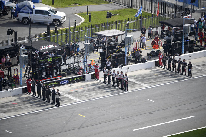 Crew members stand on pit road during the singing of the national anthem before a NASCAR Xfinity Series auto race at Daytona International Speedway Saturday, Feb. 16, 2019, in Daytona Beach, Fla. (AP Photo/Phelan M. Ebenhack)