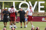FILE - In this Aug. 5, 2019 file photo, Washington's offensive line coach, Bill Callahan, center, talks with tackle Hugh Thornton (69) during NFL football training camp in Richmond, Va.  The Washington Football Team will return to Richmond for the start of training camp this summer. The club and city on Friday, June 4, 2021 announced a limited engagement from July 27-31. (AP Photo/Steve Helber)