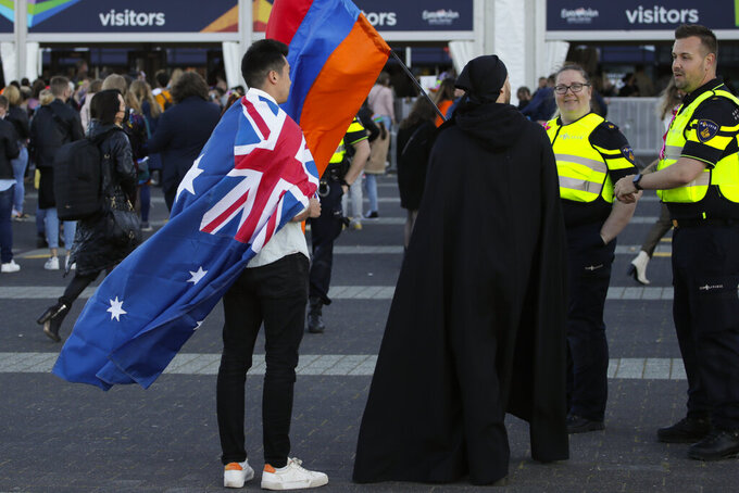 A man wearing the Australian flag talks to police officers ahead of the first semifinal of the Eurovision Song Contest at Ahoy arena in Rotterdam, Netherlands, Tuesday, May 18, 2021.The competition featuring 39 national songs from nations across Europe as well as Australia and Israel is one of the largest events staged in Europe since the global pandemic began and comes as the continent begins to tentatively ease coronavirus lockdown measures. A crowd of 3,500, tested ahead of time, will be allowed into the Ahoy arena. The number represents a fraction of its capacity to watch the performances live. (AP Photo/Peter Dejong)