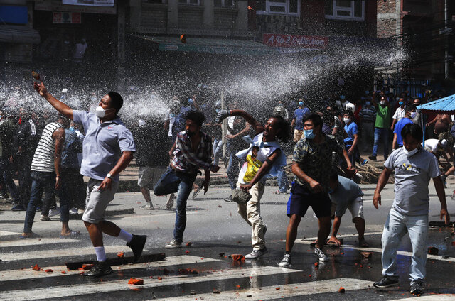 Nepalese protesters defying a government coronavirus lockdown to take part in a religious festival clash with riot police, in Lalitpur, Nepal, Thursday, Sept. 3, 2020.A 5-story-high chariot holding a statue of the deity Rato Machindranath was built but parked for months because of government orders not hold the annual festival due to fear over the spread of the coronavirus. The statue is normally pulled around the city for a month. Police officers in riot gear blocked the protesters when they moved the chariot, dousing them with water cannons. (AP Photo/Niranjan Shrestha)
