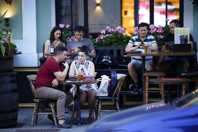People sit in an open veranda of a restaurant in Moscow, Russia, Thursday, June 24, 2021. An ambitious plan of vaccinating 30 million Russians by mid-June against the coronavirus has fallen short by a third, and the country has started to see a surge in daily new infections. So now, many regional governments across the vast country are obligating some workers to get vaccinated and requiring the shots to enter certain businesses, like restaurants. (AP Photo/Alexander Zemlianichenko)