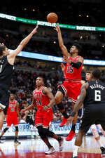 Chicago Bulls' Chandler Hutchison (15) shoots over the outstretched hand of Milwaukee Bucks' Brook Lopez, as Wendell Carter Jr. (34) and Eric Bledsoe (6) watch during the first half of an NBA basketball game Monday, Nov. 18, 2019, in Chicago. (AP Photo/Charles Rex Arbogast)