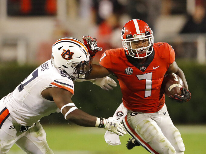 Georgia running back D'Andre Swift (7) fends off Auburn linebacker Deshaun Davis (57) during the second half of an NCAA college football game Saturday, Nov. 10, 2018, in Athens, Ga. (AP Photo/John Bazemore)