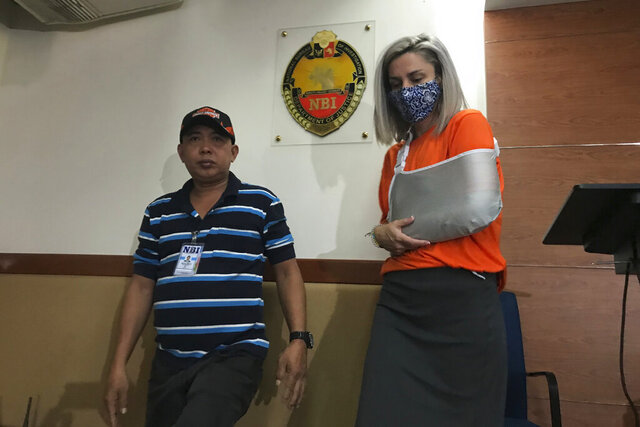 Jennifer Talbot wears a face mask as she is escorted by an agent of the National Bureau of Investigation Wednesday, Feb. 19, 2020 in Manila, Philippines. The American woman charged with human trafficking for allegedly attempting to smuggle a 6-day-old baby out of the Philippines inside a sling bag was arrested on an additional count of kidnapping, authorities said. (AP Photo/Vicente Gonzales)