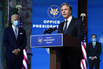 President-elect Joe Biden listens as his Secretary of State nominee Tony Blinken speaks at The Queen theater, Tuesday, Nov. 24, 2020, in Wilmington, Del. Biden's first wave of Cabinet picks and choices for his White House staff have prized staying power over star power, with a premium placed on government experience and proficiency as he looks to rebuild a depleted and demoralized federal bureaucracy.(AP Photo/Carolyn Kaster)