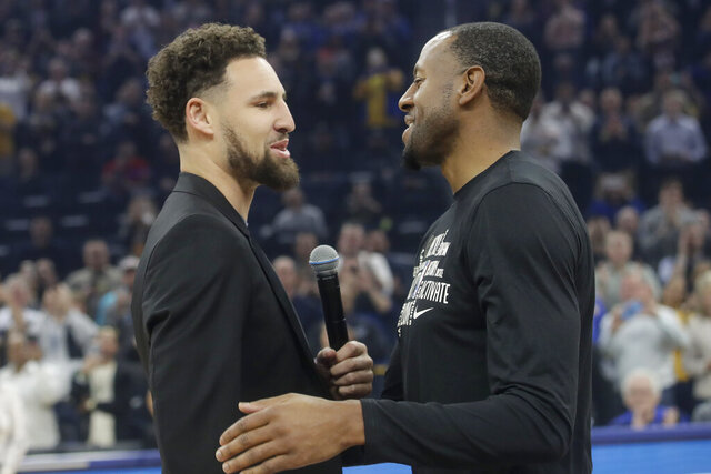 Injured Golden State Warriors guard Klay Thompson, left, greets Miami Heat guard Andre Iguodala as they address the crowd before their teams' NBA basketball game in San Francisco, Monday, Feb. 10, 2020. (AP Photo/Jeff Chiu)