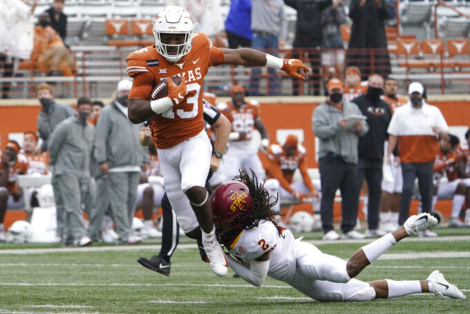 Texas wide receiver Brennan Eagles (13) is hit by Iowa State defensive back Datrone Young (2) after a catch during the first half of an NCAA college football game, Friday, Nov. 27, 2020, in Austin, Texas. (AP Photo/Eric Gay)