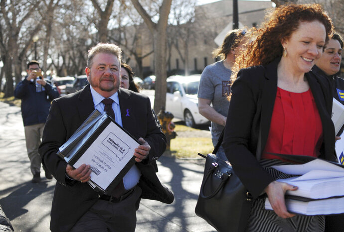 FILE - In this Feb. 23, 2016, file photo, Terri Bruce, left, walks toward the state Capitol in Pierre, S.D. Bruce said a new South Dakota bill to ban public school teaching on gender identity in elementary and middle schools would have unintended consequences and send a message to transgender children that