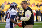 FILE - In this Dec. 20, 2015, file photo, Denver Broncos wide receiver Emmanuel Sanders (10) talks with former Pittsburgh Steelers lineman Tunch Ilkin before an NFL football game in Pittsburgh. Ilkin, a Turkis-born two-time Pro Bowl offensive lineman with the Pittsburgh Steelers in the 1980s who went on to become a beloved member of the organization's broadcast team, died on Saturday morning, Sept. 4, 2021, the team said. He was 63. Ilkin, who revealed last fall he was fighting amyotrophic lateral sclerosis (also known as Lou Gehrig's Disease), had been hospitalized recently with pneumonia. (AP Photo/Don Wright, File)