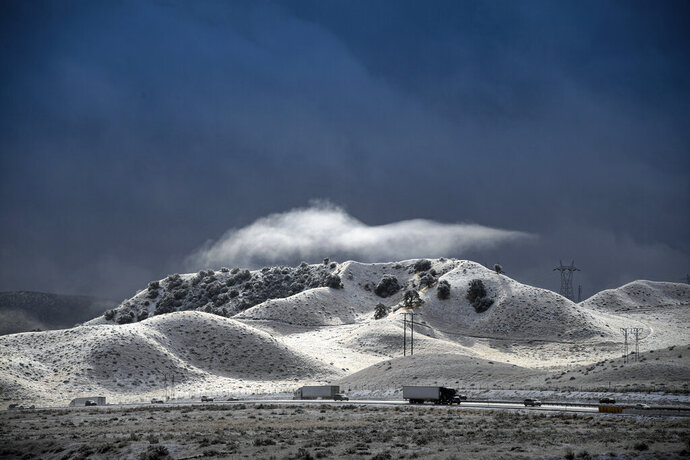 A dramatic sky opens up between snow squalls along the Interstate 5 freeway near Gorman, Calif., Wednesday, Nov. 27, 2019. Plows were running and CHP was escorting traffic in an attempt to keep the freeway open as long as possible. (David Crane/The Orange County Register via AP)