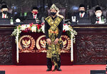 In this photo released by Indonesian Presidential Palace, Indonesian President Joko Widodo, wearing a face mask as a precaution against the new coronavirus outbreak, stands on the podium to acknowledge the parliament members after delivering his national address in Jakarta, Indonesia, Friday, Aug. 14, 2020. Indonesia's president called on all citizens to turn the COVID-19 crisis into an advancement opportunity and pledged health care reforms in an address Friday ahead of the country's 75th anniversary of independence. (Agus Suparto/Presidential Palace via AP)