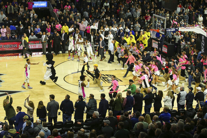 Providence Friars fans storm the court as their team defeated Seton Hall in an NCAA college basketball game Saturday, Feb. 15, 2020, in Providence, R.I. The fans had to be sent off the court as the game was not over, the clock still had 0.2 seconds left. (AP Photo/Stew Milne)