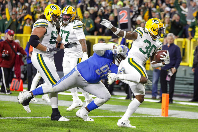 Green Bay Packers running back Jamaal Williams (30) runs for a touchdown while breaking a tackle byf Detroit Lions defensive tackle A'Shawn Robinson during the first half of an NFL football game Monday, Oct. 14, 2019, in Green Bay, Wis. (AP Photo/Mike Roemer)