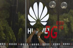 A worker wearing a mask to curb the spread of the coronavirus speaks on the phone near the Huawei logo in a store in Beijing on Wednesday, July 15, 2020. China's government accused Britain on Wednesday of colluding with Washington to hurt Chinese companies after tech giant Huawei was blocked from working on a next-generation mobile phone network. (AP Photo/Ng Han Guan)