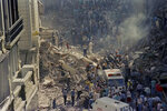 FILE- In this March 17, 1992, file photo, firemen and rescue workers walk through the debris of Israel's Embassy after a terrorist in Buenos Aires, Argentina. ( AP Photo/DonRypka-File )