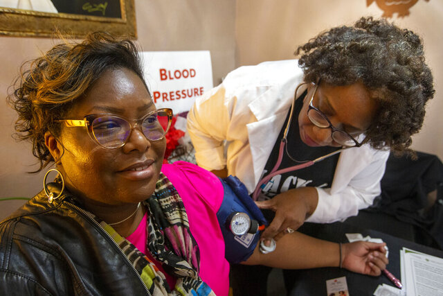 Jamilla Pinder has her blood pressure checked by Debra Barnes at the Hair, Heart and Health kick-off at Hot Seat Studio and Salon in Greensboro, N.C., on Monday, Feb. 24, 2020. (Woody Marshall/News & Record via AP)