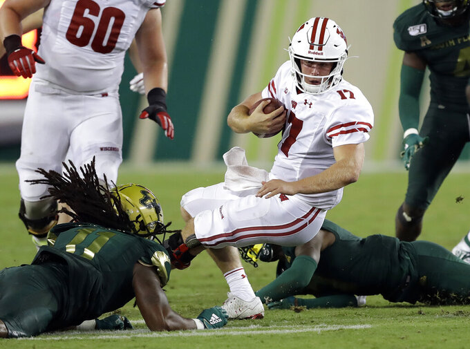 Wisconsin quarterback Jack Coan (17) gets tripped up by South Florida linebacker Dwayne Boyles, lower left, during the second half of an NCAA college football game Friday, Aug. 30, 2019, in Tampa, Fla. (AP Photo/Chris O'Meara)
