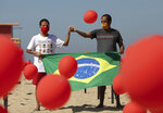 Marcio Antonio do Nascimento, right, and Lucas Cruz, the father and brother of 25-year-old Hugo do Nascimento who died from the new coronavirus, hold a Brazilian national flag as red balloons are released to honor the victims of COVID-19 in a demonstration organized by Rio de Paz, on Copacabana beach in Rio de Janeiro, Brazil, Saturday, Aug. 8, 2020, as the country heads to a milestone of 100,000 coronavirus related deaths. (AP Photo/Silvia Izquierdo)