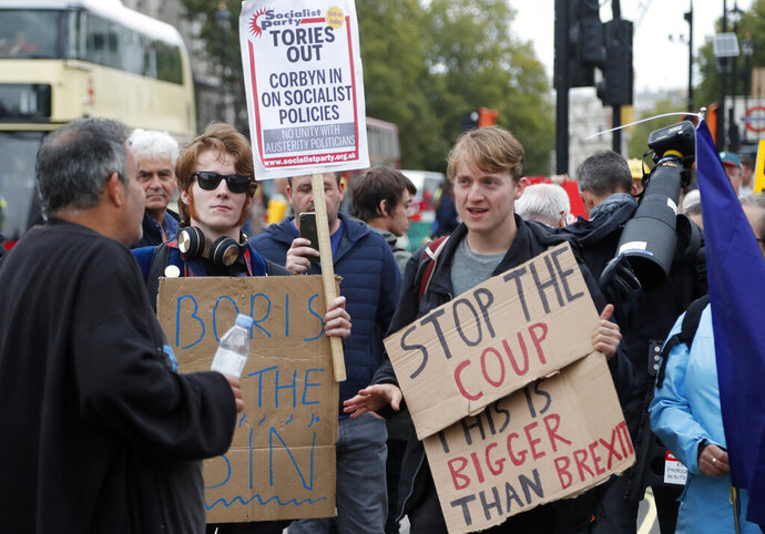 Protestors argue in parliament square in London, Monday, Sept. 9, 2019. British Prime Minister Boris Johnson voiced optimism Monday that a new Brexit deal can be reached so Britain leaves the European Union by Oct. 31.(AP Photo/Frank Augstein)