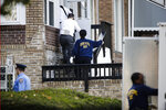 Investigators work the scene of a shooting in Philadelphia, Monday, Nov. 11, 2019. Philadelphia police are questioning a 19-year-old man in the fatal shooting of his 11-year-old brother. The boy was shot in the chest around noon at his home in West Philadelphia. He died at a hospital. (AP Photo/Matt Rourke)