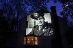 An image of veteran James Sullivan is projected onto the home of his son, Tom Sullivan, left, as he looks out a window with his brother, Joseph Sullivan, in South Hadley, Mass., Monday, May 4, 2020. Sullivan, a U.S. Army WWII veteran and resident of the Soldier's Home in Holyoke, Mass., died from the COVID-19 virus four days shy of his 100th birthday. Seeking to capture moments of private mourning at a time of global isolation, the photographer used a projector to cast large images of veterans on to the homes as their loved ones are struggling to honor them during a lockdown that has sidelined many funeral traditions. (AP Photo/David Goldman)