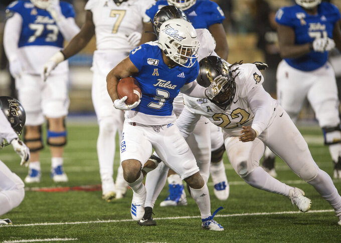 FILE - Tulsa's Shamari Brooks, left, tries to fight off Central Florida defensive lineman Kalia Davis during an NCAA college football game in Tulsa, Okla., in this Friday, Nov. 8, 2019, file photo. Most of the top college football players who opted out of the 2020 season due to the pandemic decided to leave school and launch their pro careers. But plenty of other players who opted out of last season chose to continue their college careers either at their original school or opted to transfer. Kalia Davis Davis started each of UCF's final nine games in 2019 and ended that season with 27 tackles, including eight for loss. (Brett Rojo/Tulsa World via AP, File)