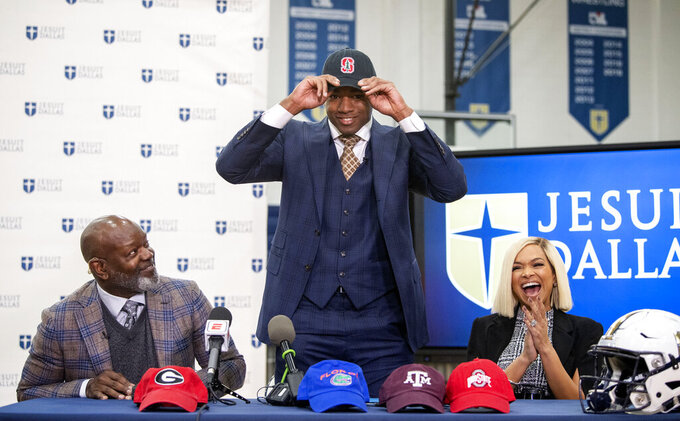Jesuit senior running back EJ Smith, son of NFL all-time leading rusher Emmitt Smith, is flanked by his parents Emmitt and Pat Smith as he announces his commitment to play NCAA college football at Stanford University during a signing day ceremony, Wednesday, Dec. 18, 2019 at Jesuit College Preparatory School in Dallas. (Jeffrey McWhorter/The Dallas Morning News via AP)