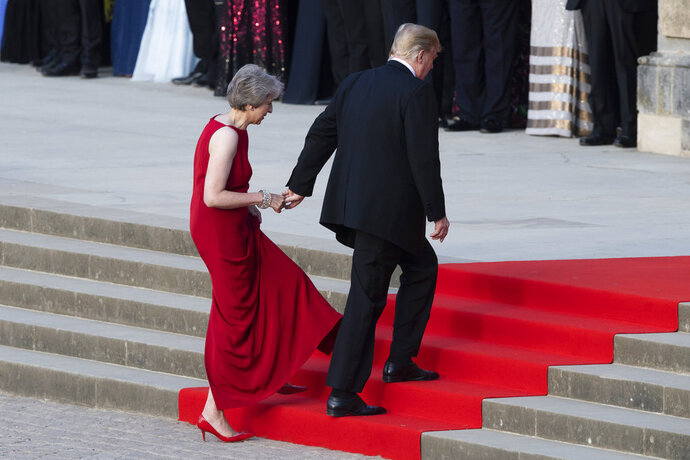 British Prime Minister Theresa May takes the hand of President Donald Trump as they walk up red-carpeted steps to enter Blenheim Palace for a black tie dinner in Blenheim, England, Thursday, July 12, 2018. (Will Oliver/Photo via AP)