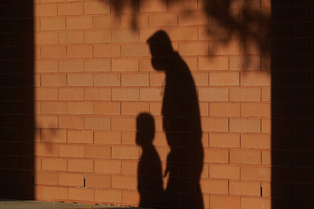 FILE - In this Friday, Oct. 9, 2020 file photo, the shadows of a school employee escorting a student are cast on the wall as they walk to a classroom on the first day of class at an elementary School in Davie, Fla. On Thursday, Jan. 14, 2021, top officials overseeing child welfare at the Department of Health and Human Services say they've seen no solid evidence to bear out warnings that serious forms of child abuse would surge during the coronavirus pandemic. (AP Photo/Wilfredo Lee)